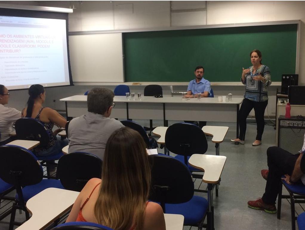 Sala de aula com diversas pessoas olhando Renata e Romani ministrando a palestra.
