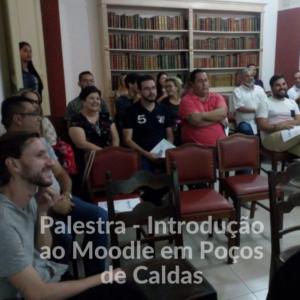 Diversas pessoas em uma sala de aula, sentadas em cadeiras, com uma estante de livros atrás. Texto escrito sobre a foto: Palestra - Introdução ao Moodle em Poços de Caldas